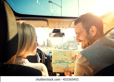 Shot of a young couple using a map while sitting in the car