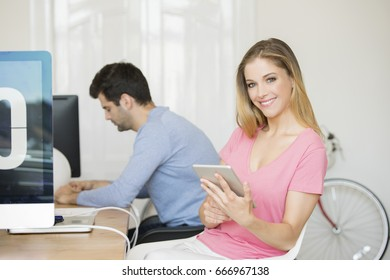 Shot of a young creative woman using digital tablet while sitting at desk in the office. Businessman working in the background.