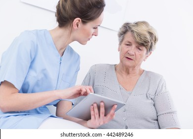 Shot of a young doctor holding a tablet and talking to her patient