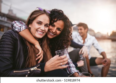 Shot of young female friends having fun with drinks on the lake. Group of people enjoying a day by the lake.