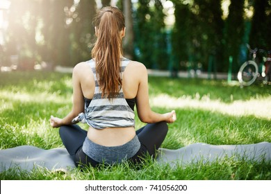 Shot of young female meditating in public city park breaking away from her daily job.