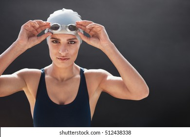 Shot of a young female swimmer isolated on black background. Fit young woman in swimming costume with copy space.