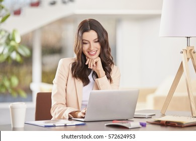 Shot of a young financial assistant female using laptop while working in the office.