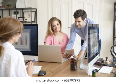 Shot of a young financial assistant and her colleagues working together on business report.