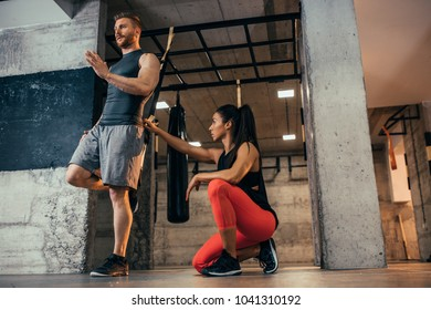 Shot of a young fit man training at the gym with his personal trainer