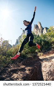 Shot of young fitness woman trail runner running and jumping on rocky mountain.