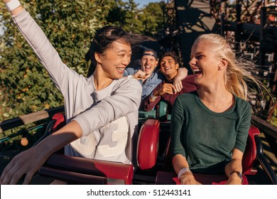 Shot of young friends enjoying and cheering on roller coaster ride. Young people having fun on rollercoaster at amusement park.