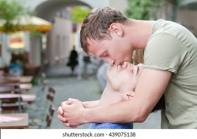 Shot of a young gay  couple  kissing in a cafe