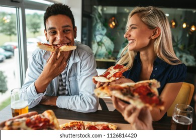 Shot of a young happy couple eating pizza in a restaurant
