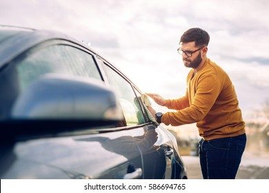 Shot of a young man cleaning the windows on his car outdoor with microfiber cloth.