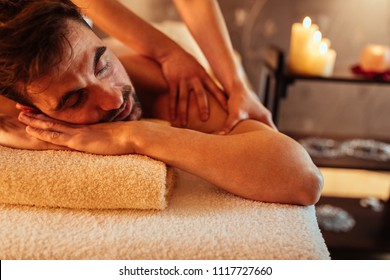 Shot of a young man enjoying a back massage at a spa