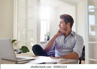 Shot of young man sitting at table looking away and thinking. Thoughtful businessman sitting home office.