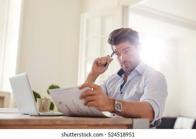 Shot of a young man sitting at table looking at documents and thinking. Business man going through paperwork at home office.