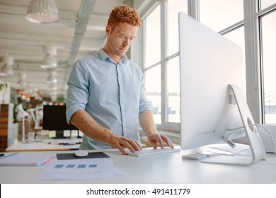 Shot of young man standing at his desk and working on computer. Businessman working in modern office.