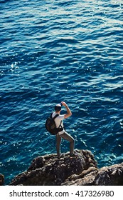 Shot of a young man traveler looking on horizon on top of a sea rocks