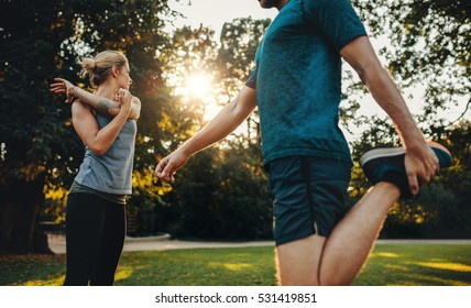 Shot of young man and woman doing stretching exercise in the park. Young couple warming up for morning workout.