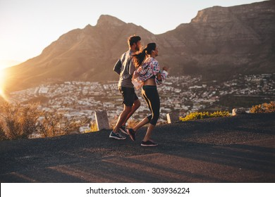 Shot of young man and woman jogging on hillside road. Young couple running in nature.