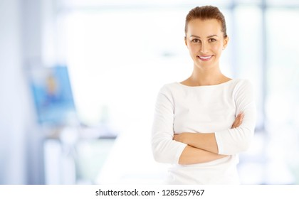 Shot of a young marketing assistant businesswoman standing with arms crossed at the office.