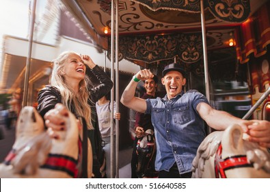 Shot of young people on amusement park ride having fun. Smiling man and woman on horse carousel ride at fairground.