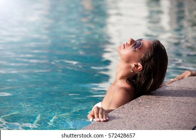Shot of a young sexy woman relaxing at a pool.