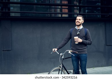Shot of a young smiling businessman going to work by bike.