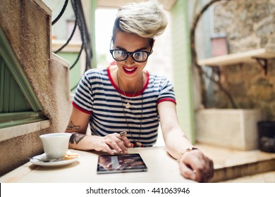 Shot of a young stylish woman using a digital tablet in a cafe  Coffee and a great book. Life's good