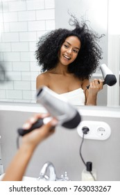 Shot of a young woman blowdrying her hair in the bathroom