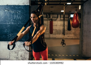 Shot of young woman exercising with trx straps at the gym