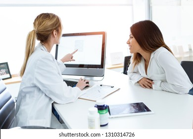 Shot of young woman gynecologist doctor showing to patient some information in computer in medical consultation.