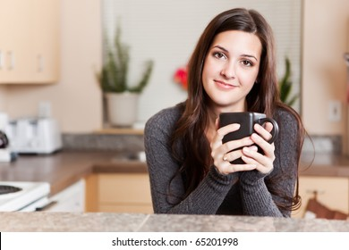 A shot of a young woman holding a cup of coffee