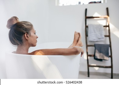 Shot of young woman lying in bathtub and looking away. Beautiful female relaxing in bathtub.