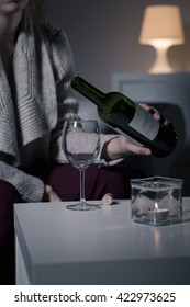 Shot of a young woman pouring herself a glass of wine