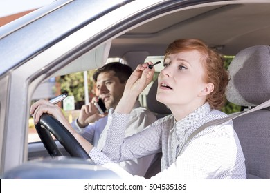 Shot of a young woman putting her mascara while driving and a businessman talking on the phone on a passenger seat