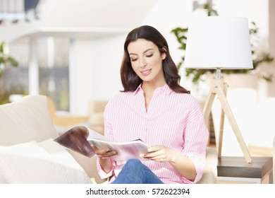 Shot of a young woman reading magazine while chill out at home.