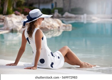Shot of a young woman relaxing by the pool.