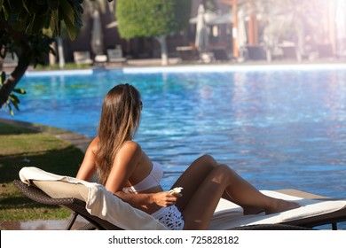 Shot of a young woman relaxing by the pool