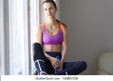 Shot of a young woman sitting at window after workout and holding a bottle of water in her hand.