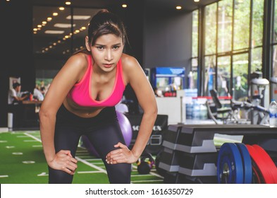 Shot of young woman in sportswear bending with her hands on knees at the gym. Fitness woman looking tired after exercising at gym.