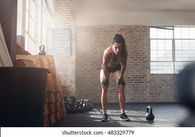 Shot of young woman in sportswear bending with her hands on knees at the gym. Fitness woman looking tired after intense crossfit workout.