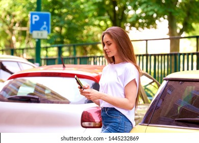 Shot of young woman standing on the street next to her car and text messaging.