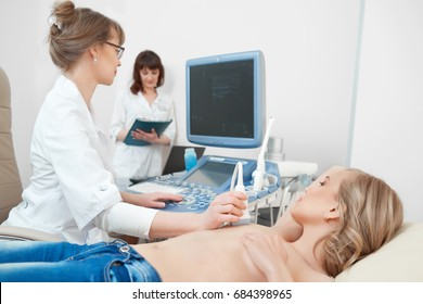 Shot of a young woman visiting her gynecologist getting breast examination with ultrasound scanner technology modern medicine cancer awareness sonogram.