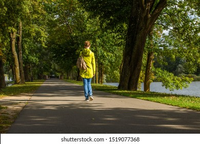 Shot of young woman wearing bright jacket and jeans, and with backpack, walking on asphalt road at levee on lake in park among green trees, at sunny fine day at early autumn, back view