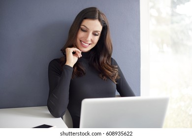 Shot of a young woman working using her laptop while working from home.