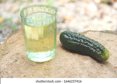 shotglass and cucumber. traditional homemade medicine. the aesthetics of alcoholism. one full shotglass and a pickle.