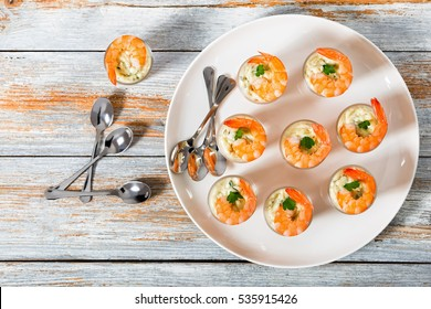 Shot-Glass Shrimp with tartar sauce - easy cocktail recipe for festive party, on white platter with spoons on old white wooden table, view from above