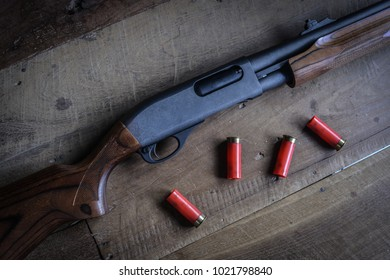 Shotgun with Bullets on Wooden Background