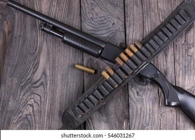 shotgun, cartridge belt with bullets, rifle Winchester, black wooden table