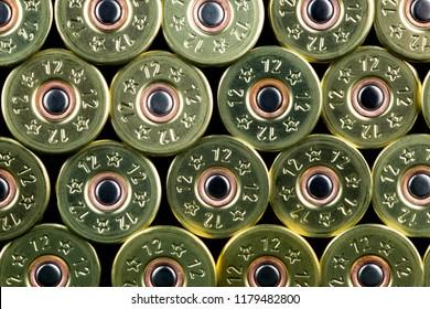 Shotgun cartridges piled against a black background