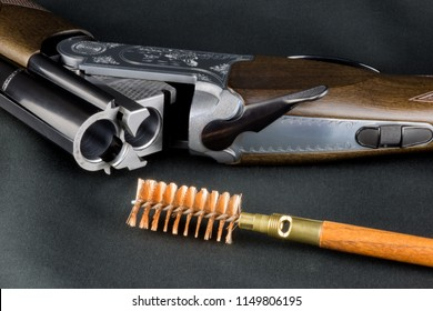 Shotgun and cleaning brush on a baize table top