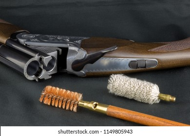 Shotgun and gun cleaning items on a baize table top